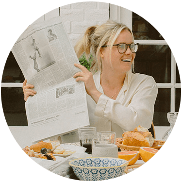 Margaux Reaume sitting at a table holding up a newspaper