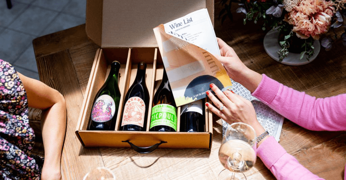 Lady with painted nails holds wine list printed on mini newspaper
